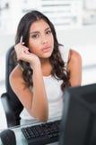 Stylo de participation mignon réfléchi de femme d'affaires regardant l'appareil-photo Images libres de droits