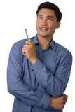 Stylo de participation réfléchi heureux d'homme d'affaires tout en regardant loin Photographie stock libre de droits
