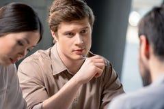 Stylo de participation sérieux de jeune homme et regarder le collègue lors de la réunion d'affaires Photo libre de droits