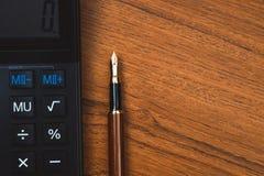 Stylo de stylo-plume ou d'encre avec la calculatrice sur la table de fonctionnement en bois Image libre de droits