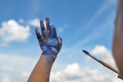 Stylo du ` s d'enfants qui a peint des nuages sur le fond du ciel bleu et une brosse dans l'autre main sur la rue 3 ans Summe images stock
