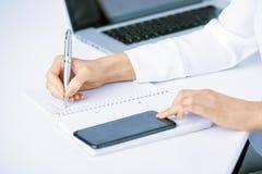 Stylo et écriture de participation de main du ` s de femme d'affaires quelque chose image stock