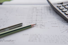 Stylo et calculatrice de crayon sur des modèles Concept architectural et d'ingénierie de logement Images libres de droits