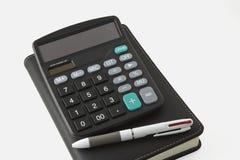 Stylo et calculatrice et carnet Images libres de droits