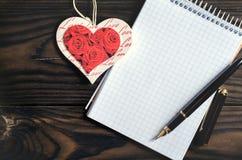 Stylo et coeur de bloc-notes sur un fond en bois Le concept de la lettre d'amour Photographie stock libre de droits