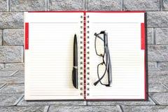 Stylo et lunettes sur un carnet Photos stock