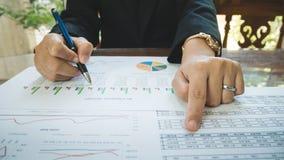 Stylo et point de prise de main de femme d'affaires au nombre sur la déclaration ou au rapport financier dans le concept d'affair Photographie stock