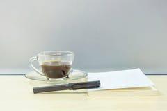 Stylo noir de plan rapproché sur le livre blanc avec du café noir dans la tasse de café transparente sur le bureau en bois brouil Image stock