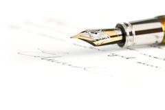 Stylo-plume d'or avec la signature photographie stock libre de droits
