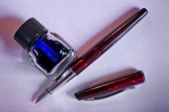 Stylo-plume, encre bleue et encrier encastré sur la feuille de livre blanc images libres de droits