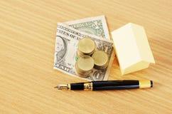 Stylo-plume et pile d'argent et de pièces de monnaie du dollar et papier à la maison pour Photos stock