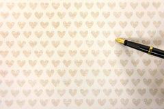Stylo-plume sur le papier de coeur d'or Image libre de droits