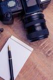 Stylo sur le bloc-notes par l'appareil-photo au bureau Photographie stock