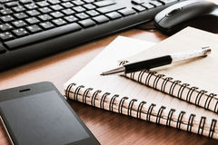 Stylo sur le carnet avec le clavier, la souris et le téléphone portable d'ordinateur Photographie stock libre de droits