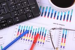 Stylo, verres, clavier d'ordinateur et tasse de café sur le graphique financier, concept d'affaires Image stock