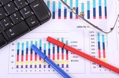 Stylo, verres et clavier d'ordinateur sur le graphique financier, concept d'affaires Photos stock