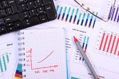 Stylo, verres et clavier d'ordinateur sur le graphique financier, concept d'affaires Images stock