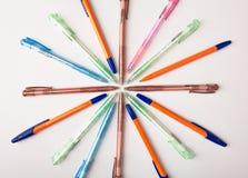 Stylos bille de différentes couleurs sur un fond blanc Photographie stock libre de droits
