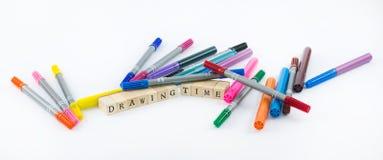Stylos colorés avec les cubes en bois qui forment les mots - temps de dessin sur un fond blanc Photo stock