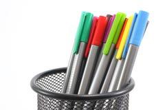 Stylos colorés dans le panier de fer sur le fond blanc Images stock