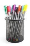Stylos colorés dans le panier de fer sur le fond blanc Image libre de droits