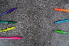 Stylos colorés sur le fond gris-foncé grunge Images libres de droits