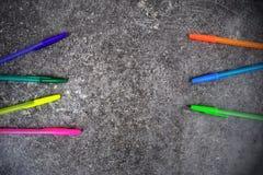 Stylos colorés sur le fond gris-foncé grunge Photographie stock