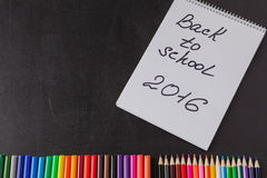 Stylos, crayons et le carnet avec le titre de nouveau à l'école 2016 sur le tableau noir d'école Photos libres de droits