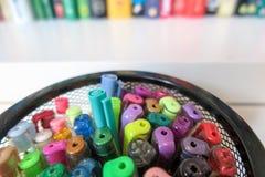 Stylos de coloration dans le récipient de maille contre l'étagère brouillée image stock