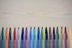 Stylos de marqueur de couleur dans la boîte en plastique sur le fond en bois de table photos libres de droits