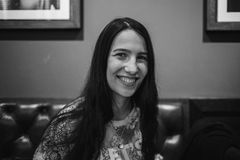 Stylowy dziewczyny obsiadanie na kanapie w kawiarni Fotografia w czarny i biały stylu Zdjęcia Stock