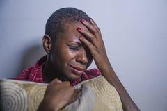 Stylu życia indoors portret młoda smutna, przygnębiona czarna afro Amerykańska kobieta siedzi w domu i obraz royalty free