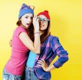 Stylu życia pojęcia ludzie: dwa ładnego potomstwa uczą kogoś nastoletnie dziewczyny ma zabawy szczęśliwy ono uśmiecha się na żółt zdjęcie stock