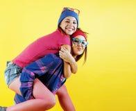 Stylu życia pojęcia ludzie: dwa ładnego potomstwa uczą kogoś nastoletnie dziewczyny ma zabawy szczęśliwy ono uśmiecha się na żółt obraz stock