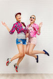 Stylu życia portret dwa młodego modniś dziewczyn najlepszego przyjaciela skacze w studiu Obraz Stock