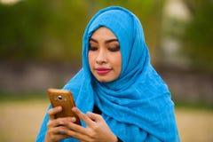 Stylu życia portret młoda szczęśliwa i piękna turystyczna kobieta w muzułmańskim hijab głowy szaliku używać telefon komórkowego o zdjęcie royalty free