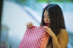 Stylu życia portret młoda szczęśliwa i z podnieceniem Azjatycka Chińska kobieta patrzeje excited w torba na zakupy kupienie przy  obraz royalty free