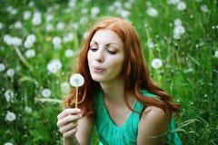 Stylu życia portret młodej wiosny mody kobiety podmuchowy dandelion w wiosna ogródzie Zdjęcie Royalty Free