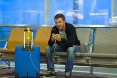 Stylu życia portret w lotnisku młody atrakcyjny i szczęśliwy turystyczny mężczyzna z walizką używać telefon komórkowego przy abor fotografia royalty free