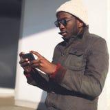 Stylu życia portreta mody młody afrykański mężczyzna używa smartphone zdjęcie royalty free