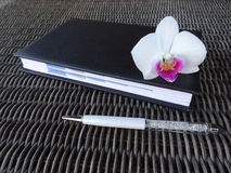 Stylus with agenda and orchid flower. Royalty Free Stock Photography