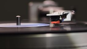 Stylus finish playing. Middle distance footage of vintage turntable starting play with focus on stylus stock video