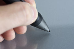 Stylus pen. Close of fingers holding a stylus digitizer pen ready to draw Royalty Free Stock Photos