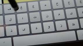 Stylus typing on tablet pc. Hand holding stylus typing fast text messages on smart tablet or phone in arabic language stock footage