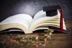 Stypendium dla edukacji pojęcia z pieniądze monetą na drewnianym z ciemną tła i skalowania nakrętką na otwartej książce obrazy royalty free