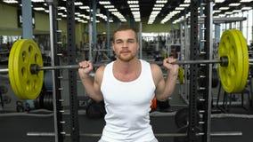 Styrkautbildning i idrottshallen grabb i t-skjortan som gör squats med en skivstång kroppsbyggare som gör övning med skivstången Royaltyfri Fotografi