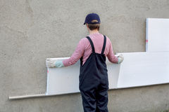Styrofoam insulation. Female worker placing styrofoam sheet insulation to the wall royalty free stock image