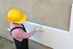 Styrofoam insulation. Female worker placing styrofoam sheet insulation to the wall royalty free stock photo