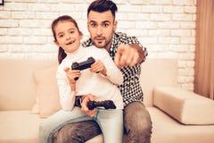Styrspak i hand Fader och dotter Spendera tid tillsammans dagfader s Man som spelar med flickan Videospel inre white arkivfoto