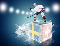 Suécia - jogo de Suíça. Jogador de hóquei Spunky no cubo de gelo Imagem de Stock Royalty Free